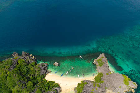 Aerial view of small isolated tropical island with white sandy beach and blue transparent water and coral reefs. Lahos Island, Caramoan Islands, Philippines. White sand beach with a coral reef, top view.