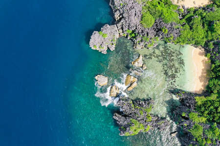 Matukad Island, Caramoan Islands, Philippines. Wild white sand beach. Summer and travel vacation concept. Rocky island with a white sandy beach, top view. Aerial top view of ocean waves, beach and rocky coastline and beautiful forest.