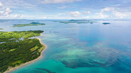 Malay archipelago with reefs and islands. Seascape with islands in the early morning, aerial drone. Beautiful landscape on the island of Luzon. Caramoan Islands, Philippines.