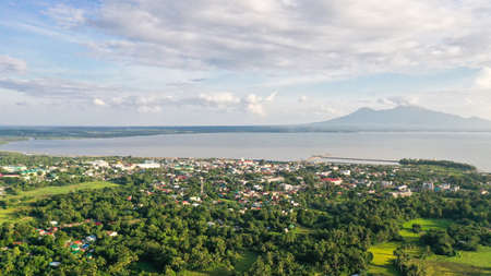 View of a small town and a volcano in the distance. Sorsogon City, Luzon, Philippines. Asian town by the sea, top view.