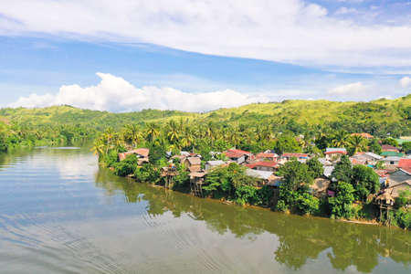 Tropical landscape in sunny weather. Village by the river. Green hills and river. Summer and travel vacation concept. The nature of the Philippine Islands.