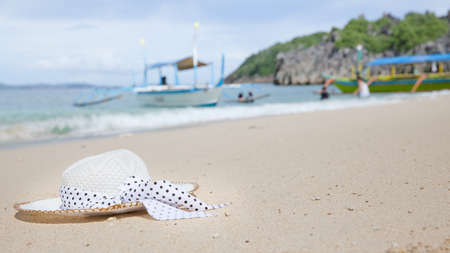 Hat on a white sandy beach. White sand. Sea traveling. Concept summer beach holiday.