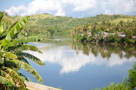 River and green hills. Beautiful natural scenery of river in southeast Asia. Countryside on a large tropical island. Small village on the green hills by the river. The nature of the Philippines.
