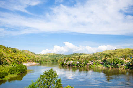 Countryside on a large tropical island. Small village on the green hills by the river. Tropical landscape in sunny weather. Village by the river. The nature of the Philippines, Samar Reklamní fotografie