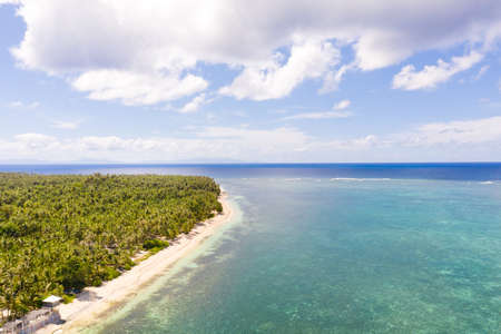 Seascape, coast of the island of Siargao, Philippines. Blue sea with waves and sky with big clouds, top view.