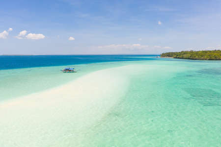 Mansalangan sandbar, Balabac, Palawan, Philippines. Tropical islands with turquoise lagoons, view from above. Boat and tourists in shallow water.