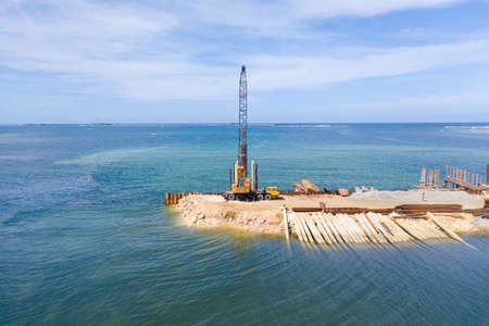 Construction of a bridge across the bay. Construction equipment on the bridge, top view. New bridge on the island of Siargao, Philippines.