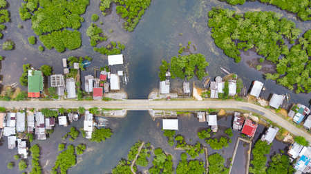 The village and the road on the water, view from above. Houses among the mangroves. Philippine village.