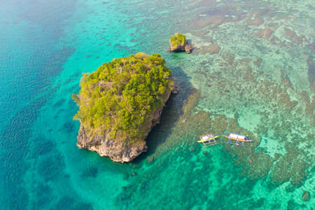 Small rocky island in the blue lagoon, view from above. Bay with turquoise water and coral bottom. Reklamní fotografie