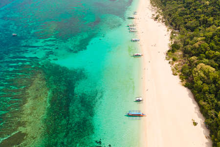 Puka Shell Beach. Wide tropical beach with white sand. Beautiful white beach and azure water on Boracay island, Philippines, top view. Tourists relax on the beach.