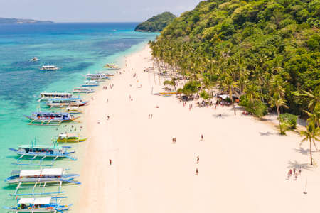 Puka Shell Beach, Boracay Island, Philippines, aerial view. Tropical white sand beach and beautiful lagoon. Tourist boats and people on the beach. People relax on the beautiful coast. Reklamní fotografie