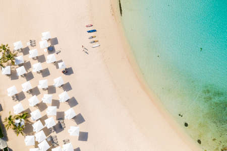 Beach umbrellas and deck chairs on the white beach. White sandy beach and clear turquoise lagoon, top view.