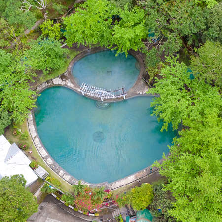 Soda Swimming Pool. Swimming pool in tropical forest on Camigin Island, Philippines. Park with swimming pool and soda water for tourists, view from above.