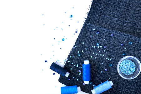 A set of materials for needlework in blue color on a white background. Beads and threads. Stock Photo