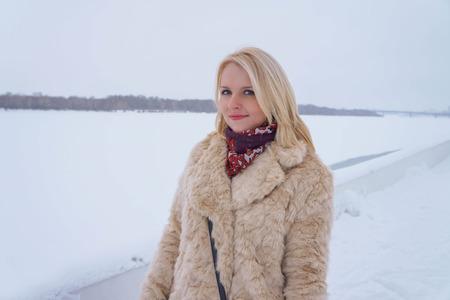 Photo of the blonde girl in the winter in a light fur coat. Standard-Bild