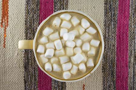 Nice Cup of coffee with marshmallow. Striped fabric background. Flat lay. Foto de archivo - 122762797