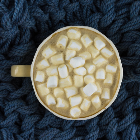 Nice Cup of coffee with marshmallow. Blue knitted background. Foto de archivo - 122762804