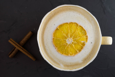 Nice Cup of coffee with dried orange. Dark background.