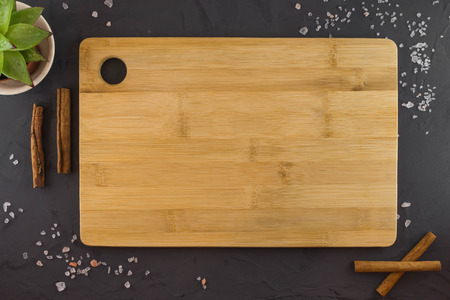 Food background with wooden cutting Board, Himalayan salt and cinnamon sticks. Dark background.