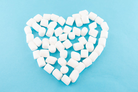 Blue paper background with a heart of marshmallow. Cozy sweet background. Imagens - 122762882