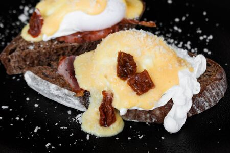 Cereal toast with fried bacon, egg Benedict and sun-dried tomato. Gourmet Breakfast with poached egg. Imagens