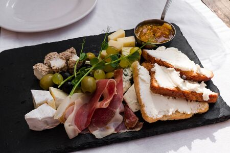 Plate with assorted cheeses, olives, Parshuto, toast and jam. Snack to wine on a white cotton tablecloth in a cafe. Imagens