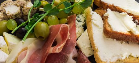 Plate with assorted cheeses, olives, Parshuto, toast and jam. Snack to wine. Imagens