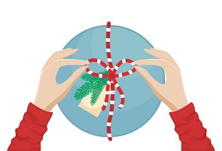 Girl packs a Christmas gift and ties a bow. Flat vector Christmas illustration. Imagens - 131119472