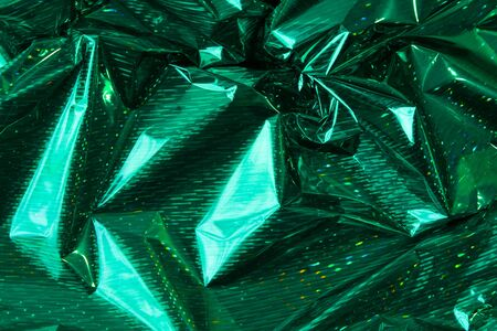 Creative photo background of green crumpled foil with highlights and shadows