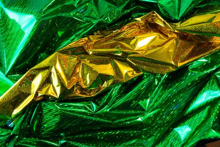 Creative photo background of green and gold crumpled foil with highlights and shadows Imagens
