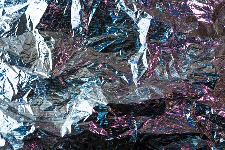 Creative photo background of crumpled foil with pink and blue highlights and shadows