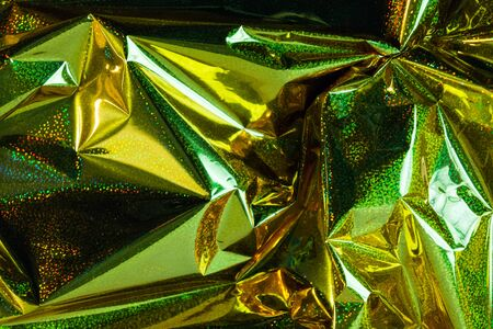 Creative photo background of gold holographic  crumpled foil with green highlights and shadows
