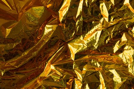 Creative photo background of gold holographic  crumpled foil with orange highlights and shadows