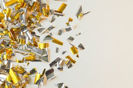 Photo background of rectangular confetti made of gold and silver foil. Place for text.