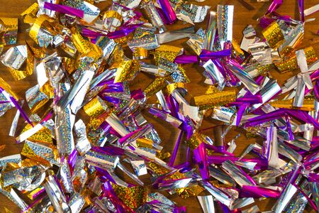 Photo background of rectangular confetti made of purple and gold foil on the wooden background. Imagens