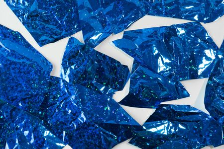 Photo background of sliced blue foil pieces on white background.