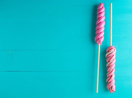 Twisted lollipops on a turquoise wooden background. Space for text. Imagens - 131119512