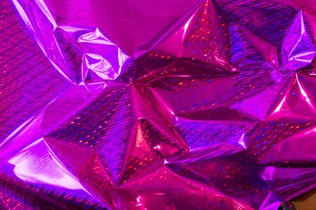 Creative purple photo background of crumpled foil with highlights and shadows. Imagens
