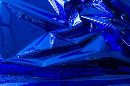 Creative photo background of blue crumpled foil with highlights and shadows