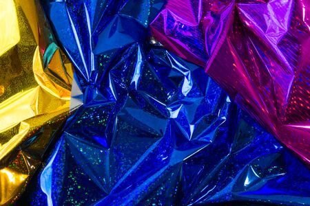 Creative photo background of blue, gold and purple crumpled foil with highlights and shadows