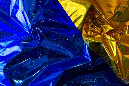 Creative photo background of blue and gold crumpled foil with highlights and shadows Imagens
