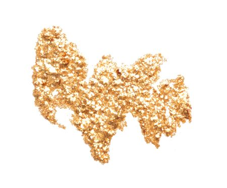 Smear small sparkling sequins on a white background. Golden glitter