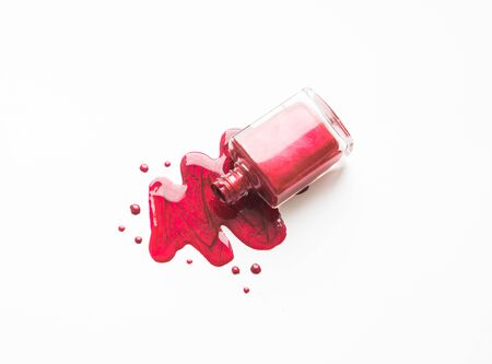 Spilled nail Polish and bottle on white background. Drops of liquid nail Polish.