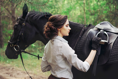 Beautiful girl rider with a black horse, dressed in a light shirt in a green forest Park. The concept of horse riding. 免版税图像