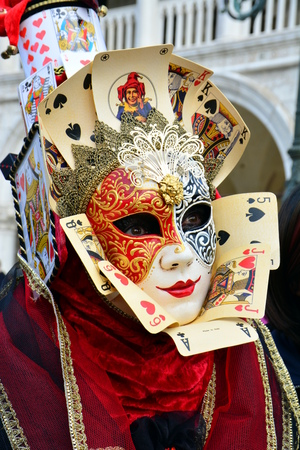 VENICE, ITALY? FEBRUARY 7: An unidentified woman dresses a two-colored mask with face and court cards During Carnival at Venice Piazza San Marco on February 7, 2015 in Venice.