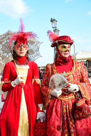 elaborate: VENICE, ITALY FEBRUARY 8: An unidentified couple of women dress elaborate red fancy dresses with masks, white gloves, jewels and hats with red feather during Venice Carnival at Piazza San Marco on February 8, 2015 in Venice Editorial