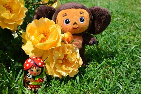 matryoshka doll: Plush toy Cheburashka (famous Russian cartoon character) stands near yellow roses and a matryoshka doll in a garden during a sunny day
