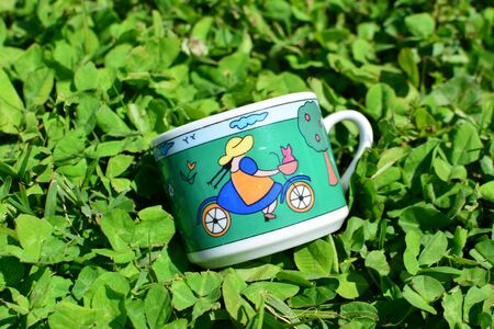 original bike: Small coffee cup, painted with a girl on bicycle, lies among clovers in a sunny day