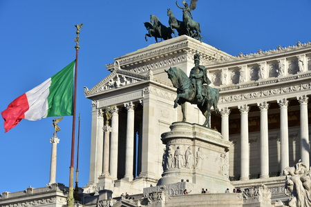 Monument to Victor Emmanuel II, Altair of the Fatherland, Equestrian statues to Victor Emmanuel II, Rome Italy with italian flag and blue sky Editorial