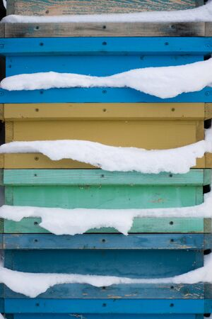 Beehives in apiary covered with snow in wintertime in the frosty dawn or the sunset. Colorful beehives with snowdrift on roofs. Foto de archivo - 132120884